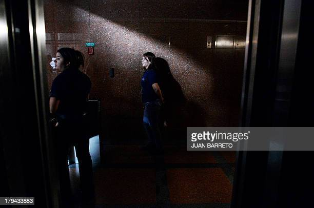 People stand on the corridor of a building during a blackout in Caracas on September 3 2013 Major power blackouts paralyzed Venezuela's capital and...