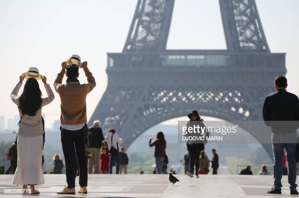 People stand on the Esplanade du Trocadero near the Eiffel tower on May 9 2017 in Paris