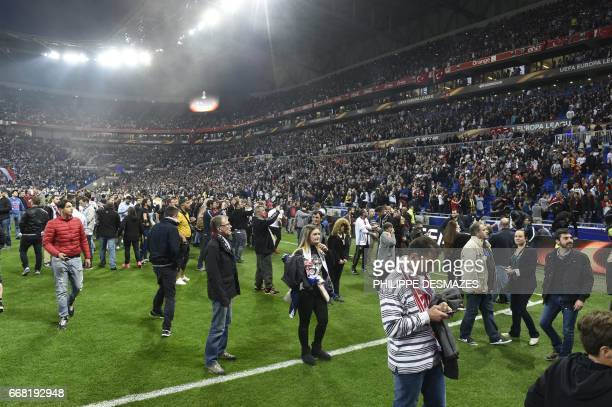 People stand on the field as Besiktas' and Lyon's fans fight in the tribune before the UEFA Europa League first leg quarter final football match...