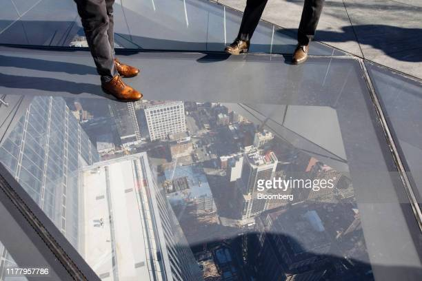 People stand on the glass floor of the Edge observation deck at 30 Hudson Yards during a media preview event in New York US on Thursday Oct 24 2019...