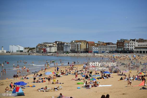 People stand on the ledge of a bathing pool in the sea backdropped by the Thanet Offshore Wind Farm in Margate south east England on May 26 after...