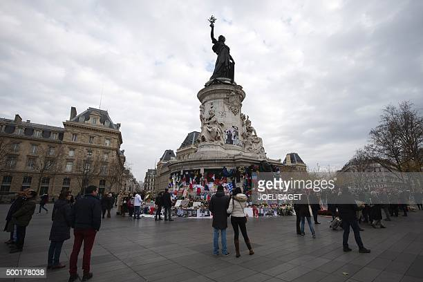 People stand on the Place de la Republique in Paris on December 6 near candles flowers and flags placed at the foot of the square's central monument...