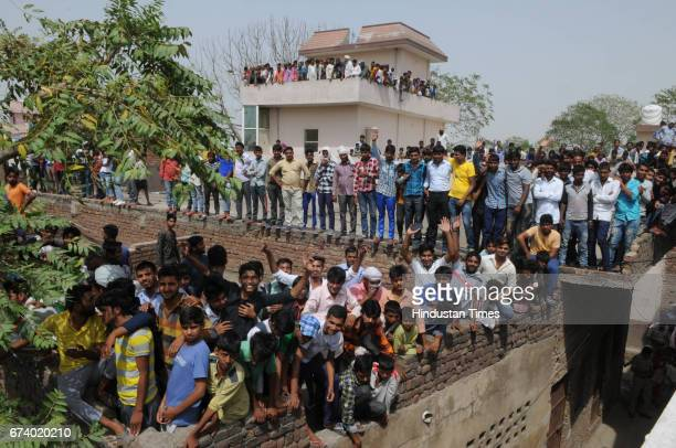 People stand on the roof and trees for seeing the leopard in Durga colony of Sohna on April 27 2017 some 25 km from Gurgaon India