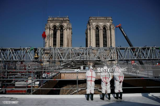 People stand on the roof of the Notre-Dame de Paris Cathedral during a visit of French President marking two years since the blaze that made the...