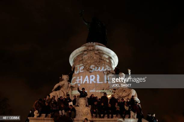 """People stand on the statue of the Republic square next to a graffiti reading """"I am Charlie"""" in Paris, on January 7 during a rally to show their..."""