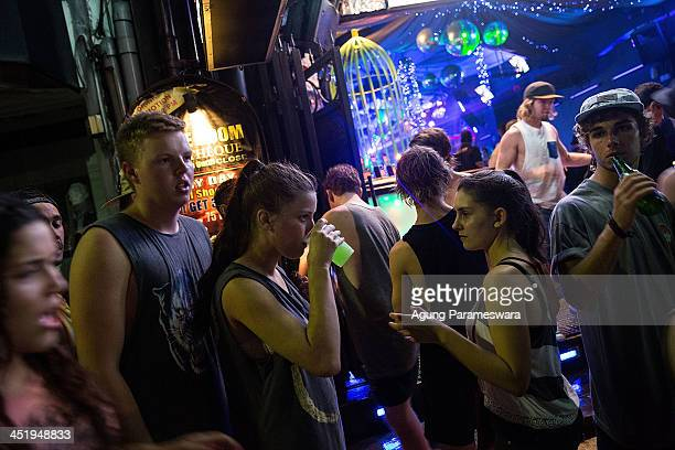 People stand on the street outside a nightclub during Australian 'schoolies' celebrations following the end of the year 12 exams on Legian Street on...