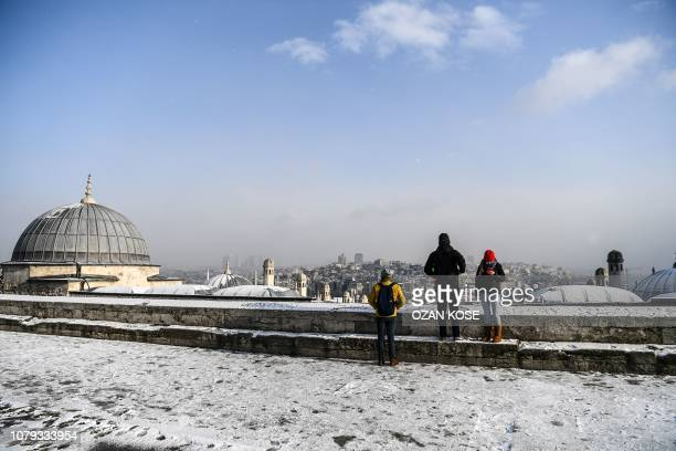 People stand on the terrace of the Suleymaniye mosque on January 8 following snowfall over the Turkish city of Istanbul
