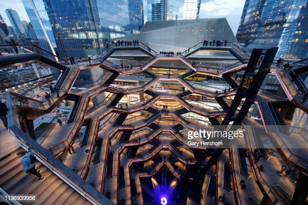 People stand on the Vessel at Hudson Yards a staircase sculpture designed by Thomas Heatherwick at sunset on March 18 2019 in New York City