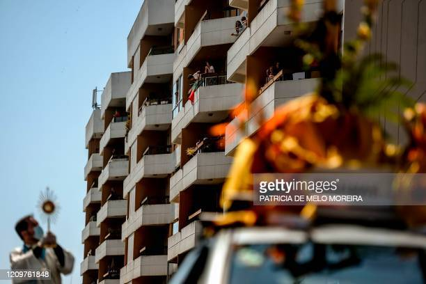 People stand on their balconies as Father Nuno Westood travels aboard a convertible Smart to pray for the faithful fulfilling the duty to stay at...