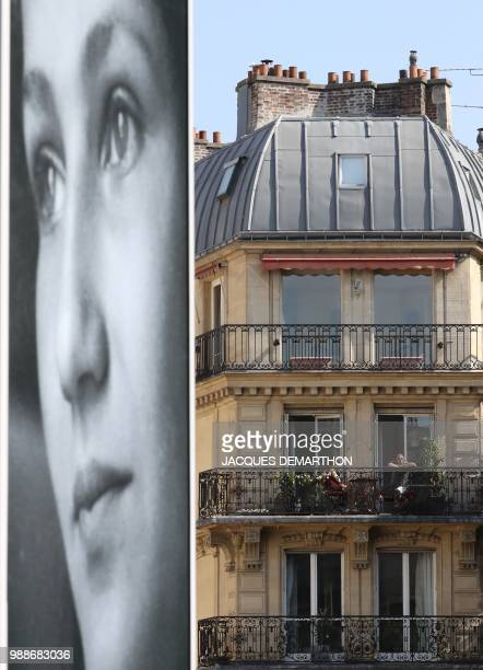 People stand on their balcony as they watch pall bearers carry the coffins of former French politician and Holocaust survivor Simone Veil and her...