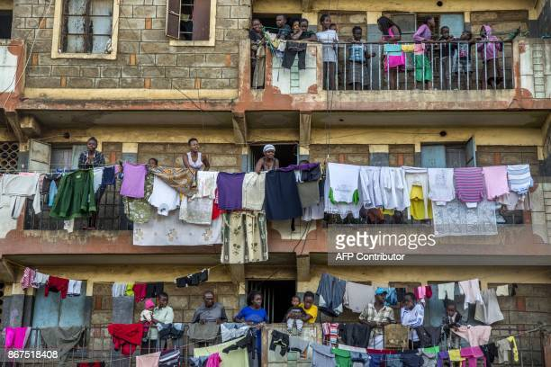 People stand on their balcony in the building where live the wife of Paul Omina Dorothy Achieng on October 28 in the Mathare slums of Nairobi a...