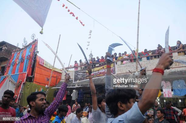 People stand on their roof to see Dussehra procession as Chief Minister of Uttar Pradesh Yogi Adityanath leads the procession from Gorakhnath Temple...