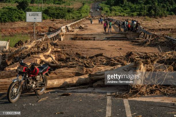 People stand on top of a broken bridge damaged during Cyclone Idai across the Lucite River on March 26 outside of Magaro Mozambique The storm caused...