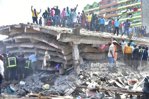 People stand on top of a collapsed sixstorey building as search and rescue continue in Nairobi on December 6 2019