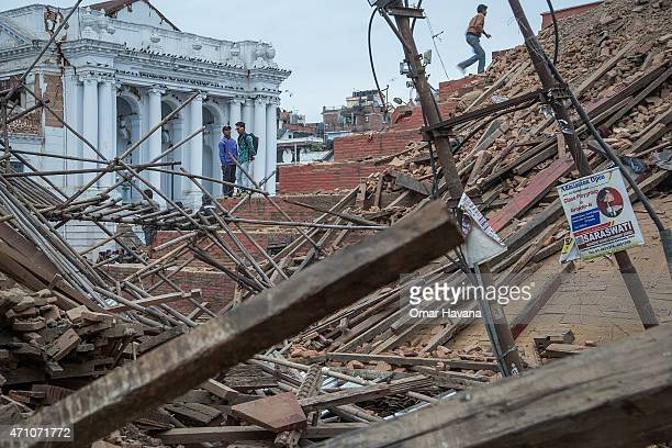 People stand on top of debris from a collapsed building at Basantapur Durbar Square watching the destruction following an earthquake following an...