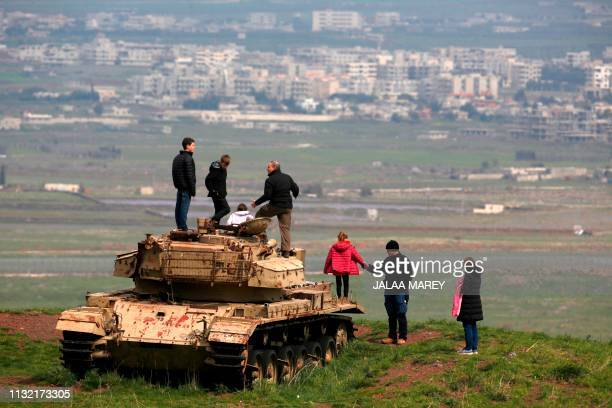 People stand on top of old Israeli tank near the Israeli Syrian border in the Israeliannexed Golan Heights on March 23 2019 facing the Syrian city of...