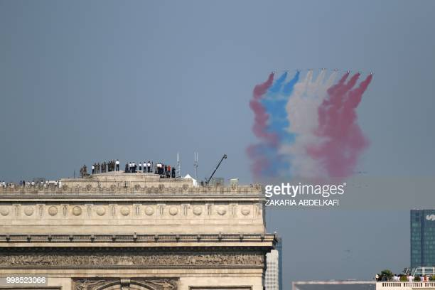 People stand on top of the Arch of Triumph as the Patrouille de France Alpha Jet perform at the start of the annual Bastille Day military parade over...