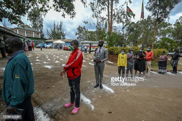 People stand on white-powder markers on the ground to adhere to social distance measures as they wait to be tested during a mass testing for COVID-19...