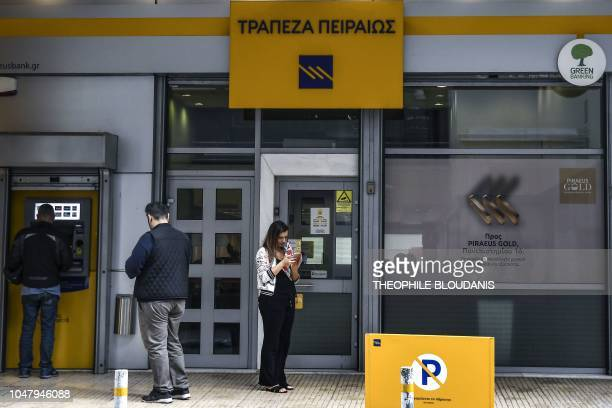 People stand outside a branch of a Piraeus Bank branch in central Athens on October 9 2018 Greece will create an asset protection scheme to help...