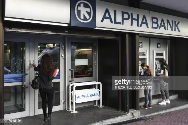 People stand outside a branch of an Alpha Bank branch in central Athens on October 9 2018 Greece will create an asset protection scheme to help major...