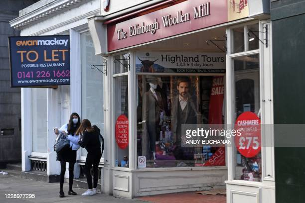 People stand outside a closed branch of The Edinburgh Woollen Mill in Edinburgh on October 9, 2020. - Edinburgh Woollen Mill appointed administrators...