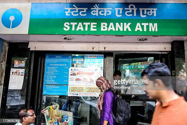 People stand outside a State Bank of India building that houses automated teller machines in Nagpur India on Sunday June 30 2013 India's services...