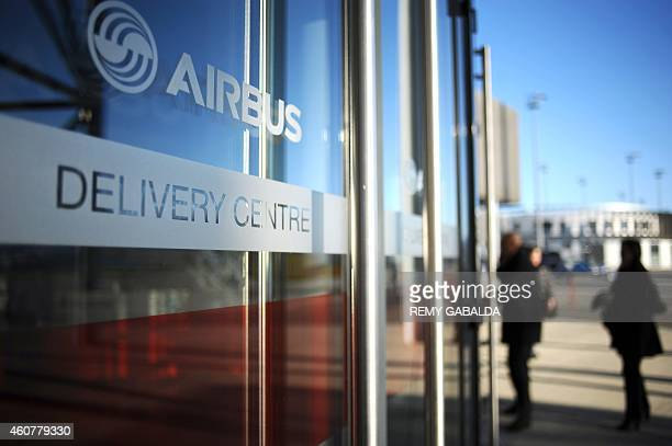 People stand outside Airbus' Delivery Center at the Airbus headquarters in Toulouse on December 22 2014 Airbus delivered its first nextgeneration...