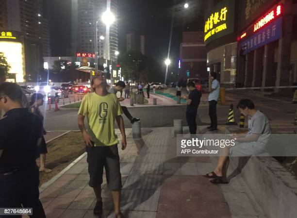 People stand outside buildings after an earthquake was felt in Xian in central China's Shanxi province on August 8 2017 The 65magnitude was centered...