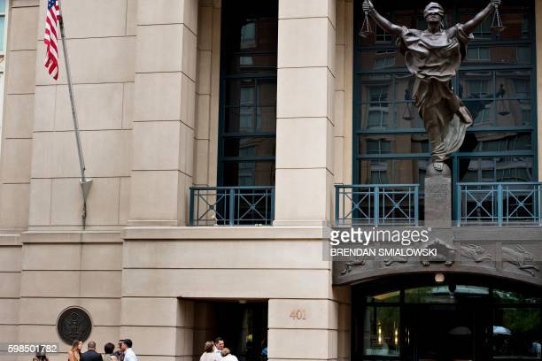 People stand outside during a sentencing hearing for Marcel Lehel Lazar a hacker known as Guccifer at the Albert V Bryan US federal courthouse...