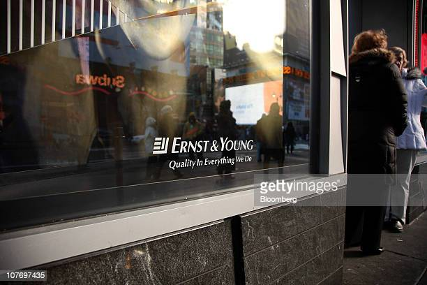 People stand outside Ernst & Young LLP'S headquarters building in New York, U.S., on Monday, Dec. 20, 2010. Ernst & Young LLP may be sued for fraud...