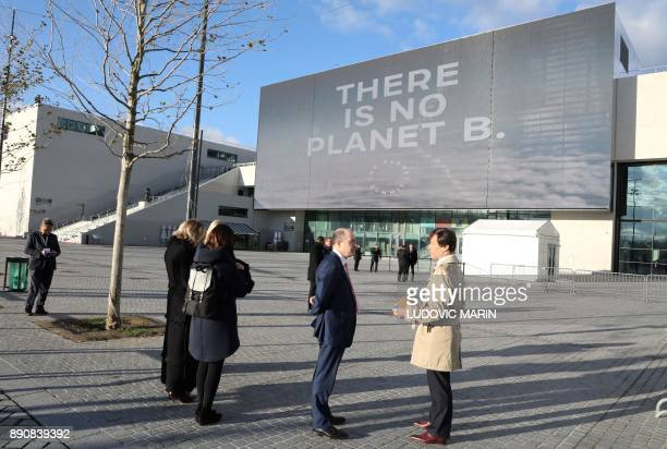 People stand outside La Seine Musicale venue on l'ile Seguin in BoulogneBillancourt west of Paris on December 12 2017 during the One Planet Summit...