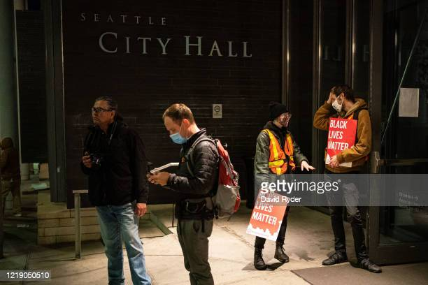 People stand outside of Seattle City Hall after demonstrators marched inside as a group led by Seattle City Council member Kshama Sawant on June 9,...