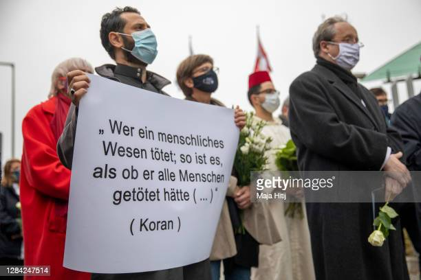 People stand outside the Austrian Embassy in an event organized by the Central Council of Muslims In Germany as a peace gathering following the...