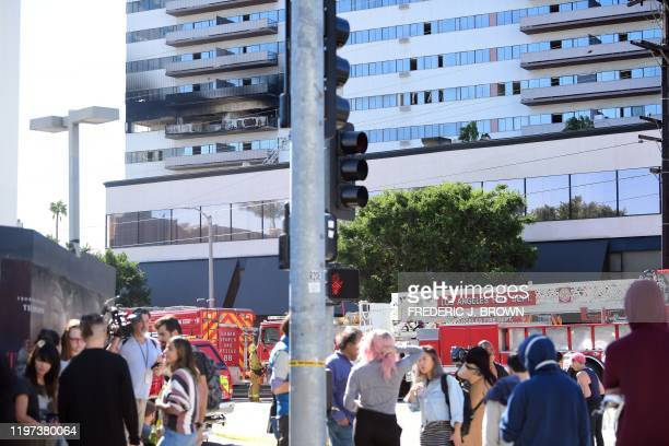 People stand outside the building after a fire on January 29 2020 in Los Angeles California A fire suspected to have been started deliberately...