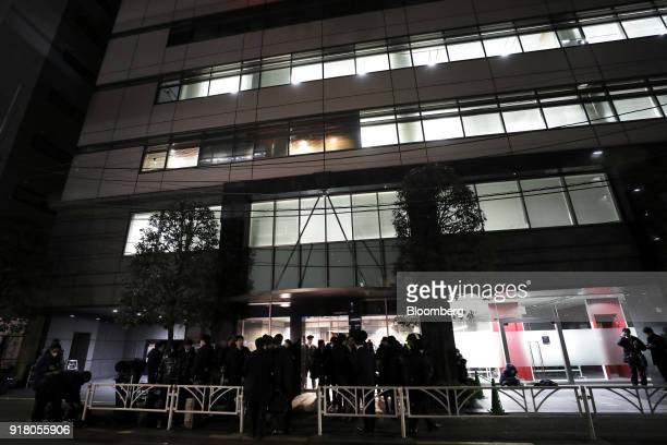 People stand outside the building that houses the headquarters of Coincheck Inc stands in Tokyo Japan on Tuesday Feb 13 2018 Cryptocurrency exchange...