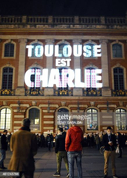 People stand outside the Capitole building in Toulouse southern France on January 9 2015 where on the facade is projected the words 'Toulouse est...