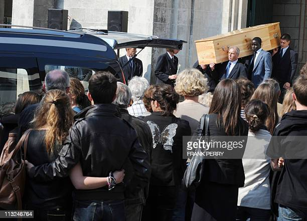 People stand outside the church of Saint Felix in the French western city of Nantes on April 28 as one of the five coffins is carried out at the end...