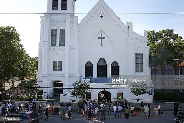 People stand outside the Emanuel AME Church after a mass shooting at the church that killed nine people on June 18 in Charleston, South Carolina. A...