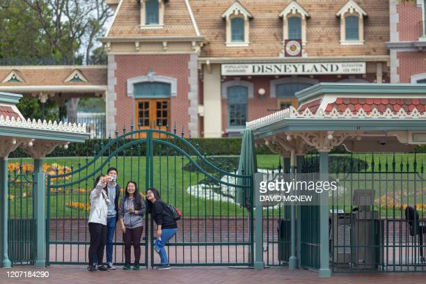 People stand outside the gates of Disneyland Park on the first day of the closure of Disneyland and Disney California Adventure theme parks as fear...