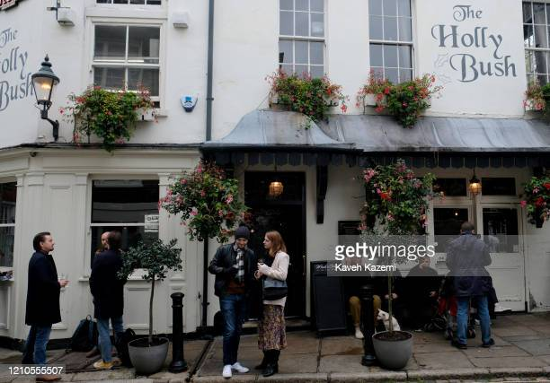 People stand outside the Holly Bush pub located in a narrow alley way in Hampstead village on November 3 2019 in London United Kingdom