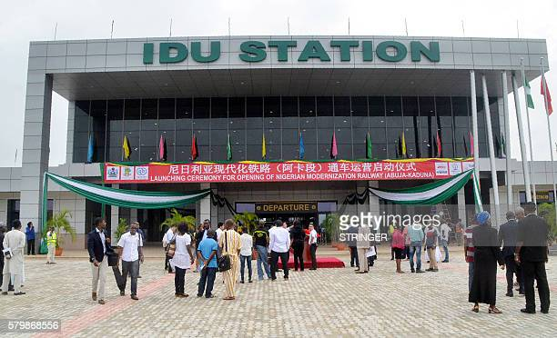 People stand outside the Idu train station during the official testrun of the newly completed AbujaKaduna night railway line in Abuja on July 21 2016...