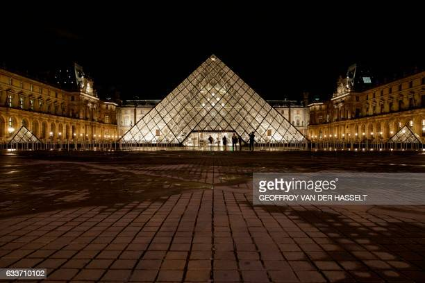 TOPSHOT People stand outside the Louvre Pyramid of the Louvre museum at night on February 3 in Paris after a French soldier patrolling at the Louvre...