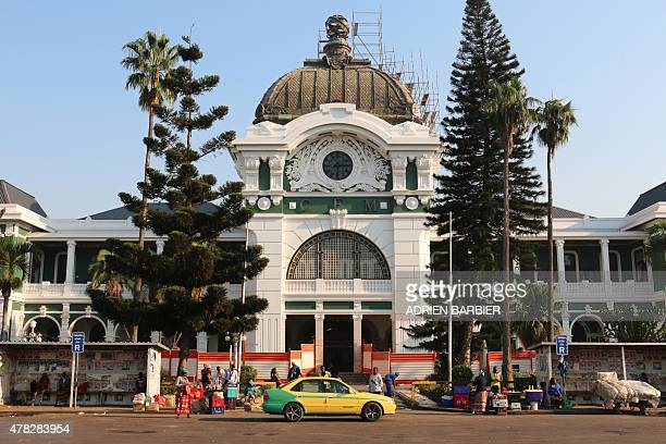 People stand outside the Maputo railway station, one of the many buildings left from the Portuguese colonial era in Maputo, on the eve of the 40th...