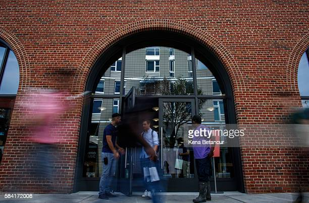 People stand outside the new Brooklyn Apple Store during a media preview in the Williamsburg neighborhood of Brooklyn on July 28 2016 in New York...