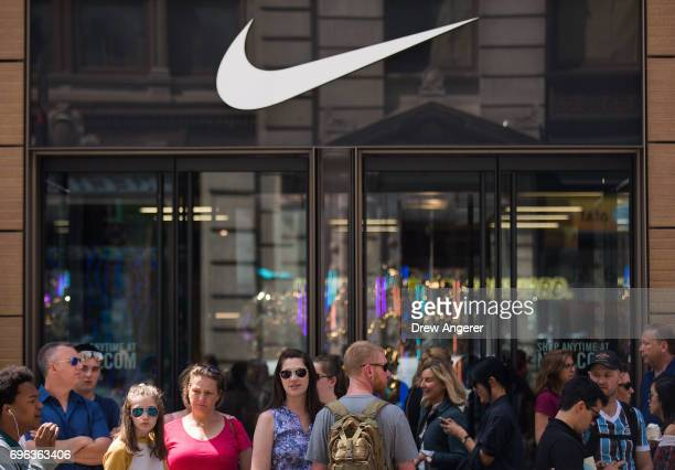 People stand outside the Nike SoHo store June 15 2017 in New York City Nike announced plans on Thursday to cut about 2 percent of its global workforce