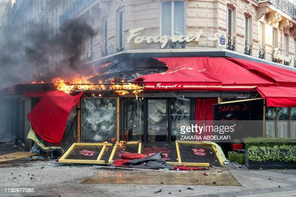 TOPSHOT People stand outside the restaurant Le Fouquet's set on fire during clashes with riot police forces on the ChampsElysees in Paris on March 16...