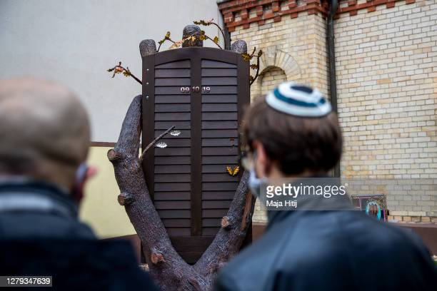 People stand outside the synagogue next to the newly unveiled memorial during commemorations on the first anniversary of the attack that left two...