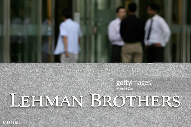 People stand outside the Tokyo branch of Lehman Brothers Holdings on September 16 2008 in Tokyo Japan The Japanese market has plummeted following the...