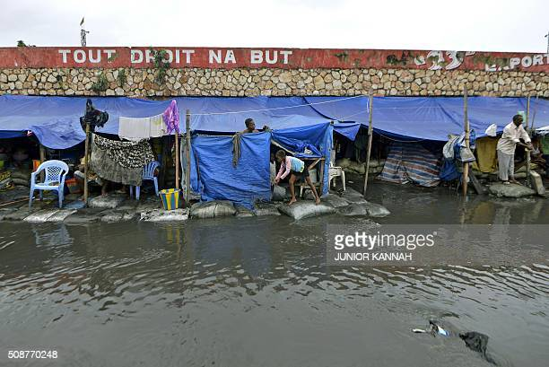 People stand outside their flooded makeshift homes in Kinshasa on February 5, 2016. For the last seven months 167 DR Congo families have lived in the...
