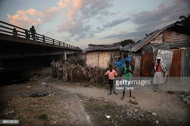 People stand outside their makeshift home constructed following the deadly January 12 magnitude 7.0 earthquake February 9, 2010 in Port-au-Prince,...